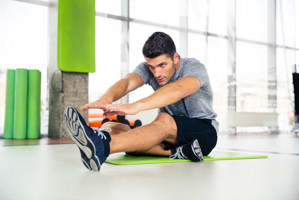 Portrait of a fitness man doing stretching exercises at gym
