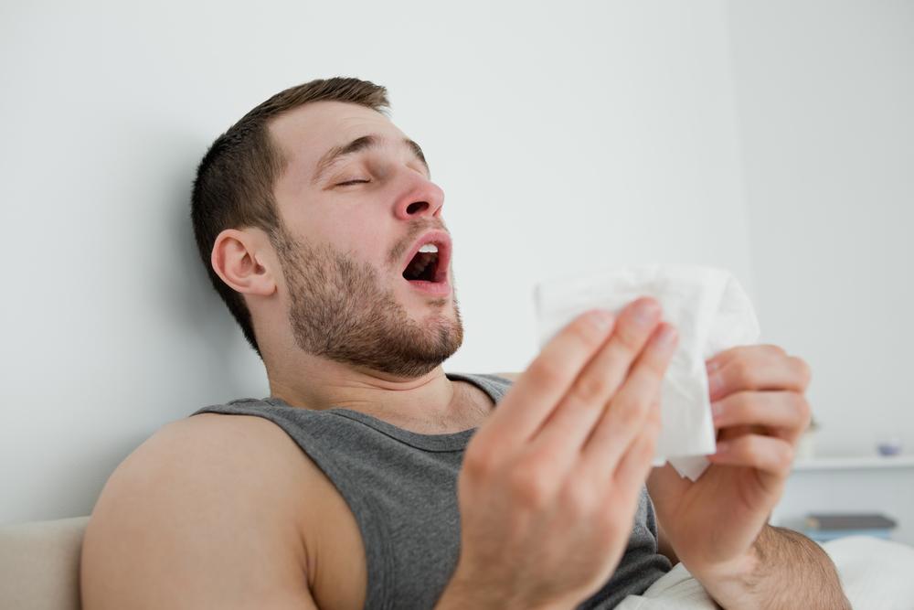 Sick man sneezing in his bedroom